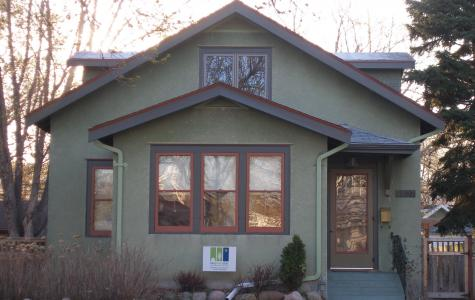A view of the completed exterior. The dormers which add so much to the upper floor are barely noticed from the street and finished to match the home. Wood storm windows and storm door replaced aluminum storms and give the house a more traditional look. Refinished vintage front door and vintage fixture along with period paint colors are details which enhance the front of the home.